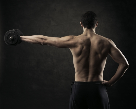 Muscular male athlete is training by lifting dumbbells Stock Photo - 18098962