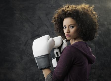 cabello rizado: Moda modelo con blancos guantes de boxeo