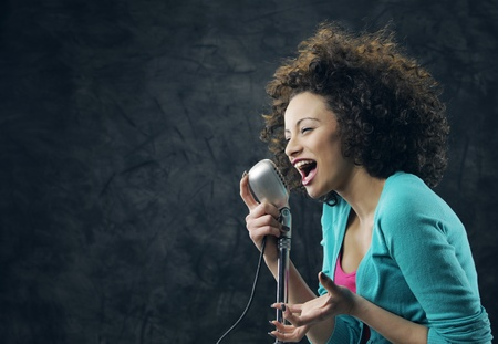 Young female singer with brown curly hair singing a song  photo