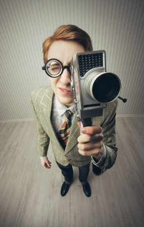 cine: Nerdy young man using old fashioned cine camera Stock Photo