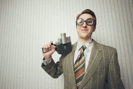 nerdy: Nerdy young man with old fashioned cine camera