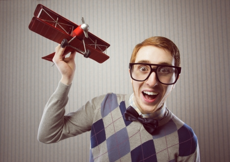 ugliness: Nerd student playing with a tin airplane Stock Photo