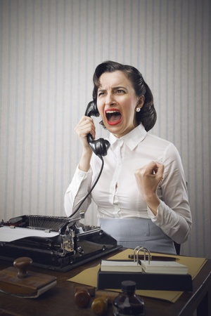 Young Business woman shouting into telephone photo