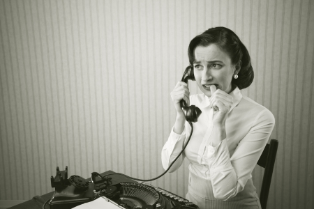 old typewriter: Woman embarrassed talking on phone at her desk Stock Photo