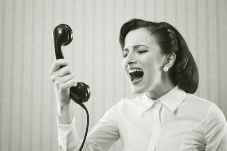 secretaria: Mujer joven que grita en teléfono Foto de archivo