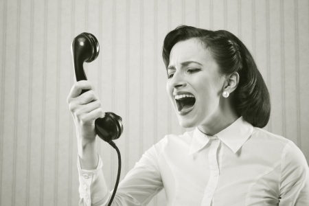 woman screaming: Young Woman shouting into telephone