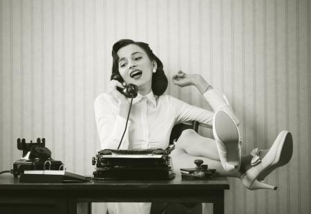 비즈니스 여자는 전화에 그녀의 책상에 그녀의 발을두고