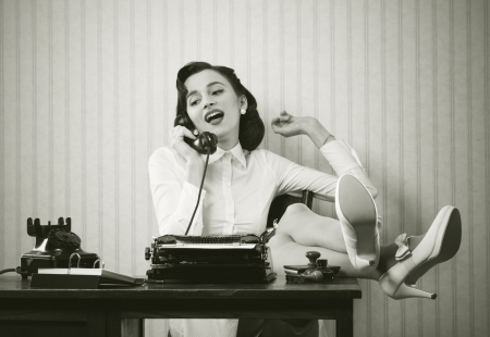 old phone: Business woman puts her feet up on her desk on the phone