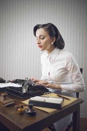 the typewriter: Retro mujer de negocios escribiendo en su despacho
