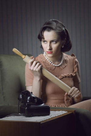 retro housewife: Angry wife waiting for her husband with a rolling pin in hand
