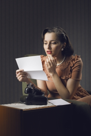 Young woman reading a letter sitting on armchair photo