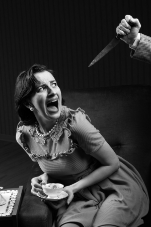 Terrified woman by a man murderess with a knife. Classic film noir style photo