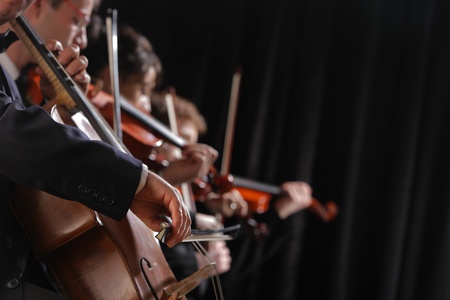 Symphony concert, a man playing the cello, hand close up