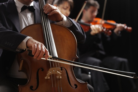 violin: Symphony concert, a man playing the cello, hand close up Stock Photo