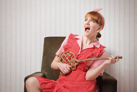beater: portrait of retro pin up housewife playing on her guitar carpet beater Stock Photo