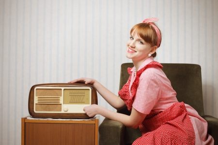 Old-fashioned young woman listening to the radio photo