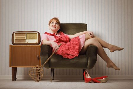 Young retro housewife resting on a chair Stock Photo - 18628480