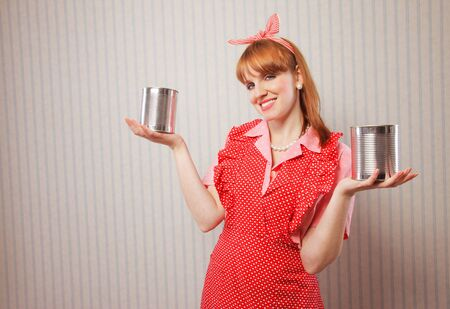 housewife holding two tin food cans Stock Photo - 18628483