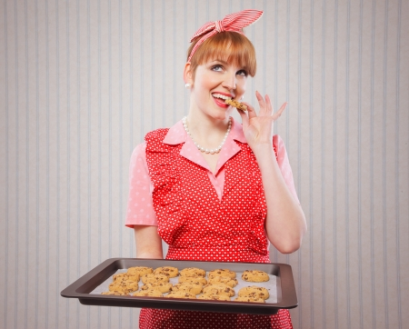 Retro housewife holding cookie tray full of chocolate cookie  photo