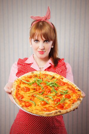 Young housewife holding a vegetarian pizza for lunch photo