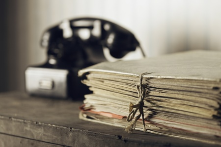 landline phone: A desk with documents, Old phone on the background