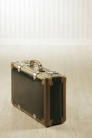 Old-fashioned suitcase alone in a room or station. Stock Photo - 18654248