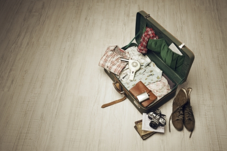 open suitcase: Vintage suitcase open on a wood floor in an empty room