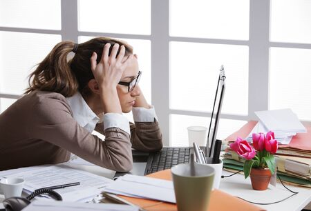 emotional stress: Young and beautiful businesswoman tired from work in the office.Woman holding her head