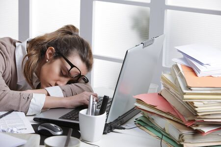 emotional stress: Tired businesswoman sleeping on the desk, in front of the computer screen.