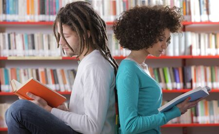african descent: Two students learning together indoors in library