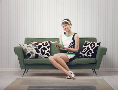 Girl sitting on the couch with a book photo