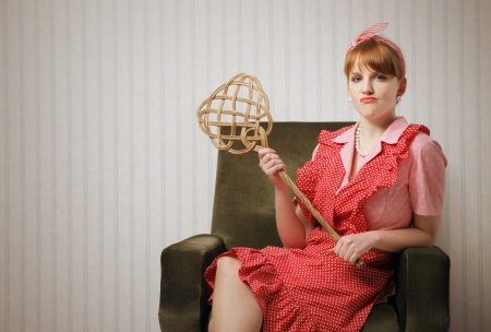 stereotypical housewife: Ironic portrait of a housewife retro sitting in an armchair