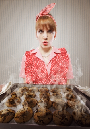 woman baking: Retro housewife burnt the cookies Stock Photo