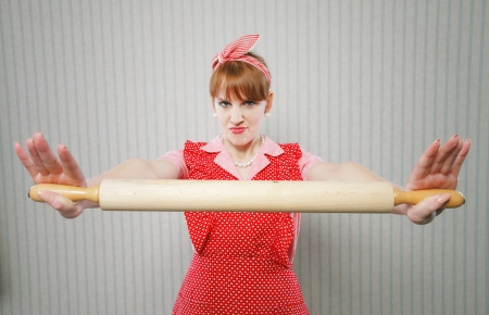 Retro housewife holding a rolling pin, ready to fight photo