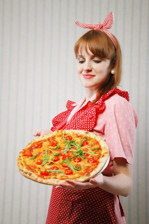 Young housewife holding a vegetarian pizza for lunch Stock Photo - 19167083