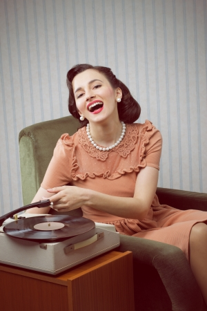 Smiling woman listening to music from a turntable photo