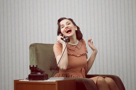 Cheerful woman talking on landline phone photo