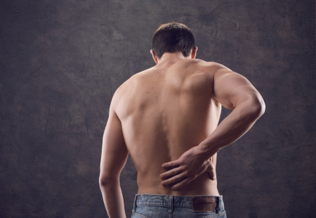 male shirtless from behind holding hand to spot of back pain photo