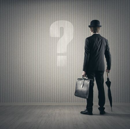 Businessman looking  at big question mark photo