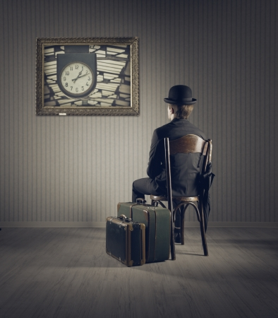 Business man sitting on old chair,  checking time for his travel photo