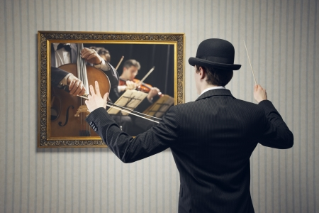 Male orchestra conductor directing with his baton in concert, conceptual image photo