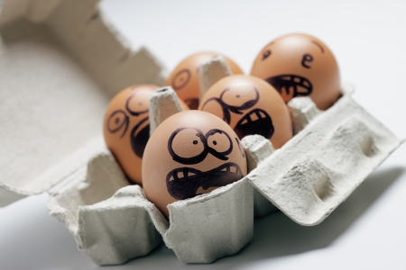egg carton: funny eggs with facial expression: scared, screaming and being terrified. Stock Photo