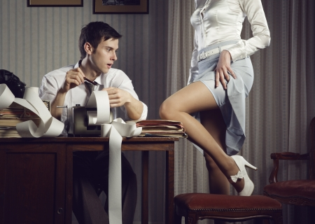 business woman legs: Young sexy woman shows a leg for business man at desk
