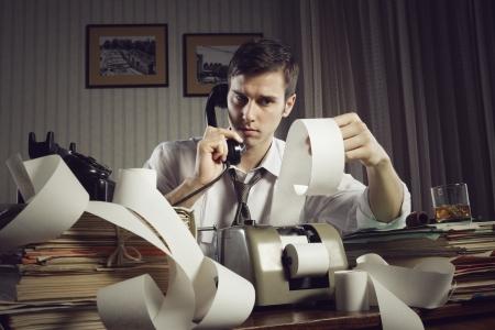 tax bills: An male accountant at telephone  preparing income taxes