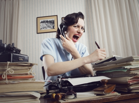 Stressed businesswoman shouting into telephone  is sitting at a table full of paperwork photo