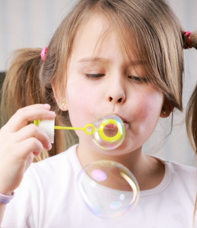 children playing with toys: Portrait of a little girll blowing bubbles Stock Photo