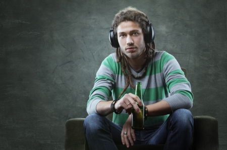 dreadlock: Relaxed young guy listening to music with headphones Stock Photo