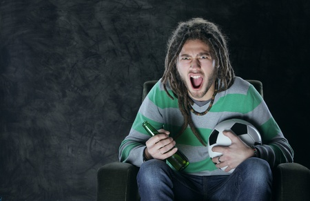 Young adult man watching football on television: Goal! photo
