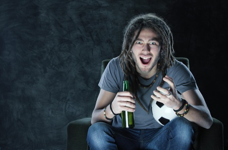 supporter: Young adult man watching football on television: Goal!