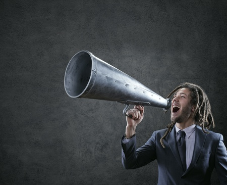 Young businessman yelling trough a vintage megaphone photo